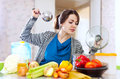 Woman cooking veggie lunch with laddle beautiful young in kitchen at home Royalty Free Stock Image