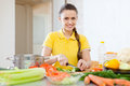 Woman cooking veggie lunch with laddle beautiful young in kitchen at home Royalty Free Stock Photo