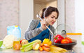 Woman cooking veggie lunch with laddle happy beautiful young adult in kitchen at home Stock Images
