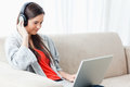 A woman on the couch with her laptop and listening to headphones Stock Photo