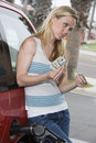 Woman Counting And Handing Out Money At Fuel Station Royalty Free Stock Photography