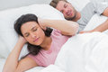 Woman covering ears while her husband is snoring next to Royalty Free Stock Photos