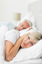 Woman covering ears while man snoring in bed closeup of a women men at home Stock Photography