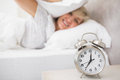 Woman covering ears with pillow with alarm clock in foreground mature sleepy bed at home Stock Images