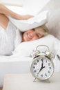 Woman covering ears with pillow with alarm clock in foreground mature sleepy bed at home Royalty Free Stock Images