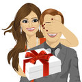 Woman covering her boyfriend's eyes standing behind man with gift Royalty Free Stock Photo