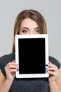 Woman covering her face with blank tablet computer screen Royalty Free Stock Photo