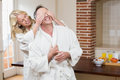 Woman covering her husband eyes in the kitchen Royalty Free Stock Photo