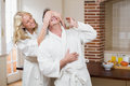 Woman covering her husband eyes in the kitchen Stock Photos