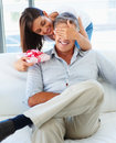 Woman covering her husband's eyes Stock Photos