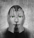 Woman covers her face with her hands and green eyes on the grunge backround Royalty Free Stock Images
