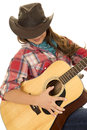 Woman cowgirl with guitar looking down strumming Royalty Free Stock Photo