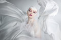 Woman with creative make-up in a white cloth flying. A girl holding a flying white cloth Royalty Free Stock Photo