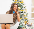 Woman with credit card using laptop near christmas tree portrait of thoughtful young Stock Photography