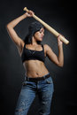 Woman criminal with bat on dark background Royalty Free Stock Photography