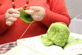Woman crocheting a bonnet hands of green with wool Royalty Free Stock Images