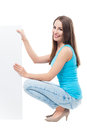 Woman crouching by blank board young over white background Royalty Free Stock Photography