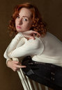 Woman crouching on chair an image of an attractive with curly red hair and freckles a Royalty Free Stock Photos