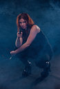 Woman crouching down aiming a gun Royalty Free Stock Photos