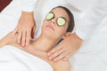 Woman with cucumber on her face gets a massage pretty girl facer Stock Photography