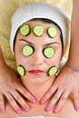 Woman with  cucumber mask getting neck massage Stock Images