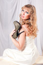 Woman cuddle shoe beautiful in a white dress high heeled shoes Royalty Free Stock Photo
