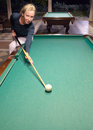 Woman with a cue behind a billiard table Royalty Free Stock Photo