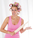 Woman with curlers and a rolling pin blond pink holding looking very upset Stock Photos