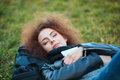 Woman with curly hair sleeping on green grass Royalty Free Stock Photo