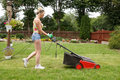 Woman cut garden the flower with an electric mower Stock Photos