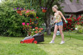 Woman cut garden the flower with an electric mower Royalty Free Stock Photos