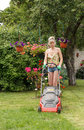 Woman cut garden the flower with an electric mower Royalty Free Stock Photo