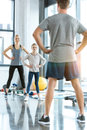 Woman and cute girl exercising with coach at fitness studio Royalty Free Stock Photo