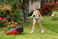Woman cuts the grass with an electric lawn mower Royalty Free Stock Images