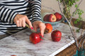 Woman cutting apples on the table Royalty Free Stock Photo