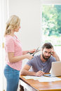 Woman cutting a credit card while tense man with bills sitting at table Royalty Free Stock Photo