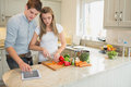 Woman cutting vegetables with man using tablet computer men in kitchen Royalty Free Stock Photo
