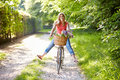 Woman on cycle ride in countryside with flowers basket having fun Royalty Free Stock Image