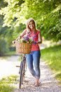 Woman on cycle ride in countryside with flowers basket smiling at camera Stock Photos