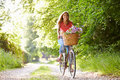 Woman on cycle ride in countryside her own with flowers basket Royalty Free Stock Image