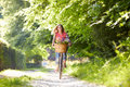 Woman on cycle ride in countryside summertime smiling to camera Royalty Free Stock Images