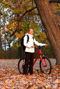 Woman cyclist with bike and backpack in morning Royalty Free Stock Images