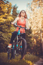 Woman cyclist rides in the forest on a mountain bike.
