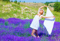 Woman dance on lavender field beautiful blond holding in hands white shawl and dancing in purple flower sunny day summer season Stock Photos