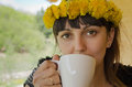 Woman with a dandelion headband made of fresh yellow dandelions sipping cup of hot coffee and looking at the camera Royalty Free Stock Photos