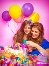 Woman with daughter open gift box happy birthday party colorful festive decorations excited faces cake candles happy Stock Images