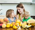 Woman with daughters eating melon happy women and peaches over table at home interior Royalty Free Stock Photo