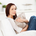 Woman daydreaming at home sitting in an armchair hugging a cushion and staring into space Stock Photos