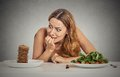 Woman deciding whether to eat healthy food or sweet cookies she craving portrait young is sitting at table grey wall background Royalty Free Stock Photography