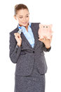 Woman deciding whether to spend or save holding a dollar bill in one hand and her piggy bank in the other with a wry expression Stock Photography
